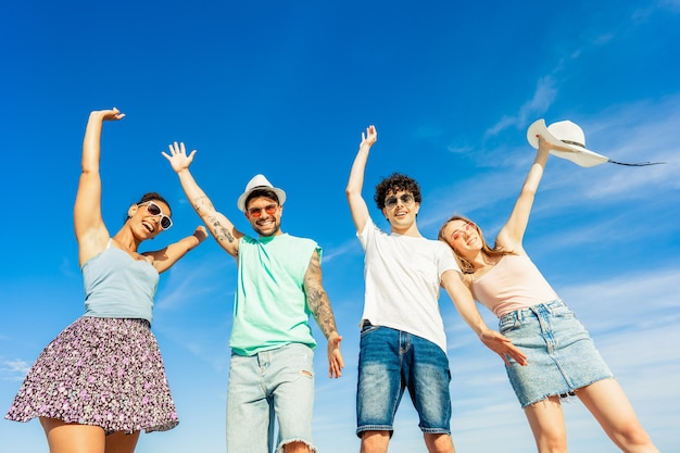 Young gen z happy multiracial friends group looking at camera for portrait in summer sea vacations. bright vivid color photograph with blue sky. diverse millennial people having fun at beach resort