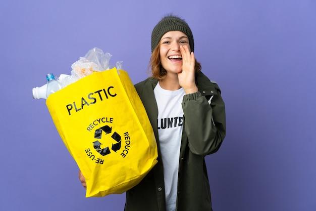 플라스틱 병으로 가득 찬 가방을 들고 어린 그루지야 소녀는 입 벌리고 소리를 재활용합니다.