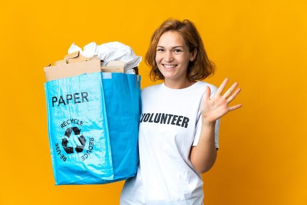 指で5を数えてリサイクルするために紙でいっぱいのリサイクルバッグを持っている若いグルジアの女の子