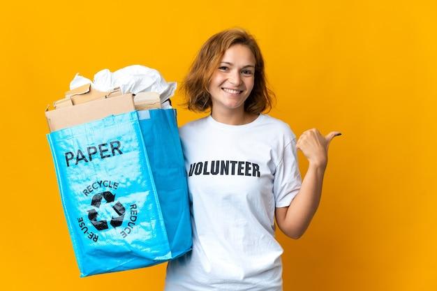 제품을 제시하기 위해 측면을 가리키는 재활용 종이로 가득 찬 재활용 가방을 들고 어린 그루지야 소녀