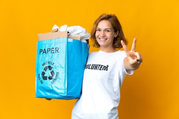 笑顔と勝利のサインを示すリサイクルのために紙でいっぱいのリサイクルバッグを持っている若いグルジアの女の子