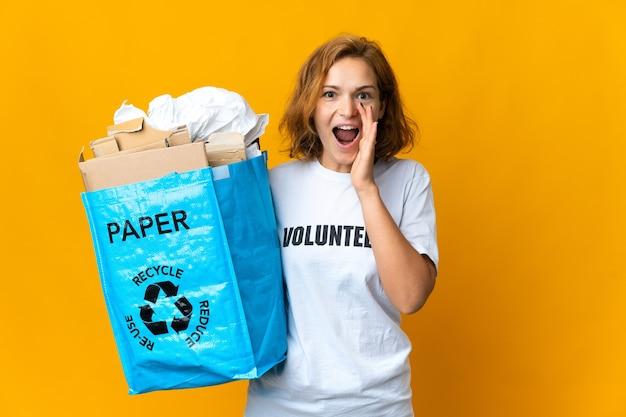 Молодая грузинская девушка с удивленным и шокированным выражением лица держит мешок для вторичной переработки, полный бумаги, которую нужно утилизировать