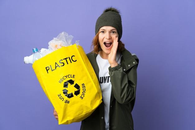 Молодая грузинка с удивлением и шокированным выражением лица держит мешок, полный пластиковых бутылок, которые нужно переработать