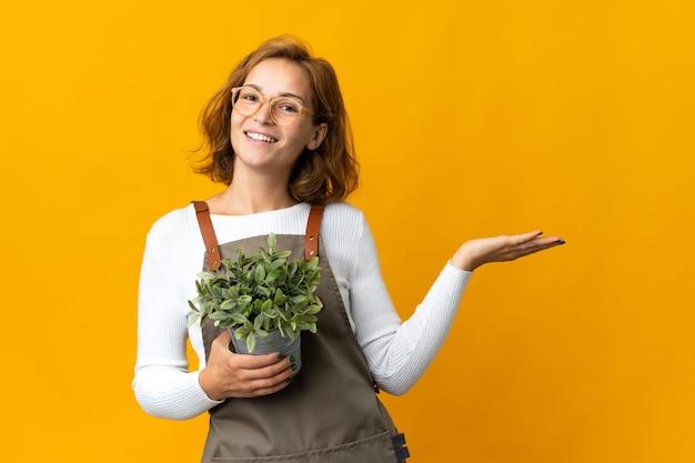 노란색 배경에 고립 된 식물을 들고 젊은 그루지야 여자가 와서 초대하기 위해 손을 옆으로 확장