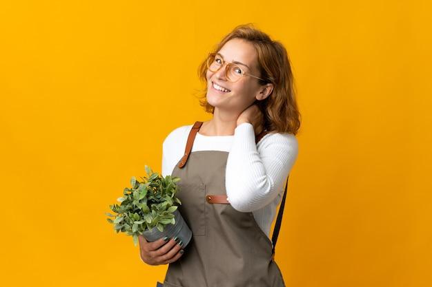 笑って黄色の背景に分離された植物を保持している若いジョージ王朝の女性