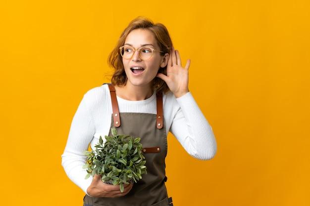 귀에 손을 넣어 뭔가를 듣고 노란색 배경에 고립 된 식물을 들고 젊은 그루지야 여자