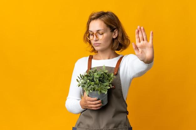 노란색 배경에 고립 된 식물을 들고 젊은 그루지야 여자는 중지 제스처를 만들고 실망