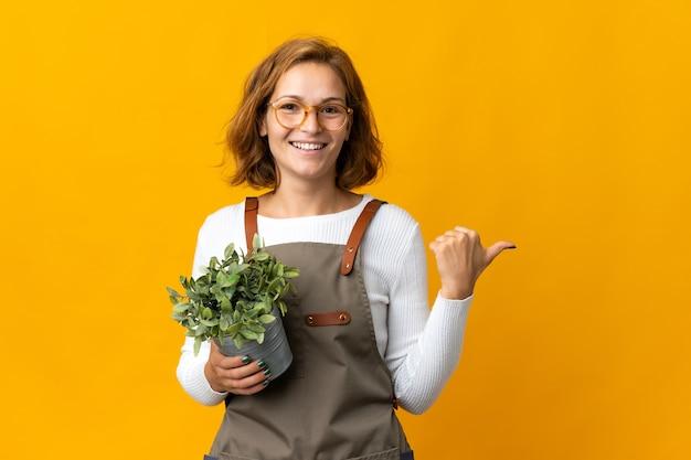 제품을 제시하기 위해 측면을 가리키는 노란색 배경에 고립 된 식물을 들고 젊은 그루지야 여자