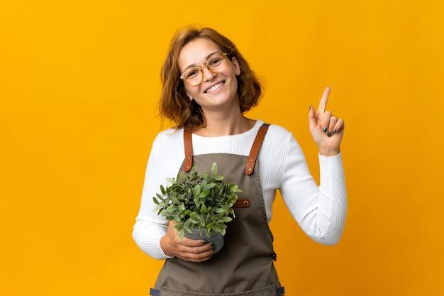노란색 배경에 고립 된 식물을 들고 젊은 그루지야 여자가 보여주는 최고의 기호에 손가락을 들어 올려