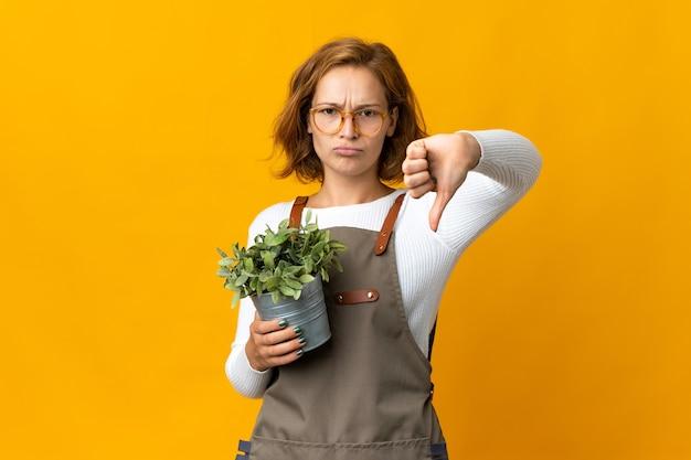 否定的な表現で親指を下に示す黄色の背景に分離された植物を保持している若いジョージ王朝の女性