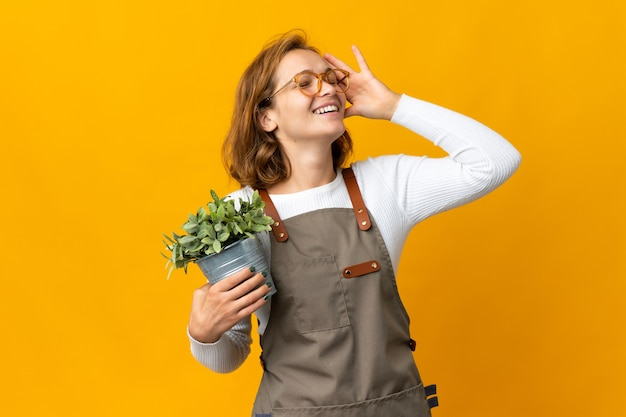 たくさん笑って黄色の背景に分離された植物を保持している若いグルジア女性