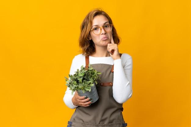 アイデアを考えて黄色の背景で隔離の植物を保持している若いジョージ王朝の女性