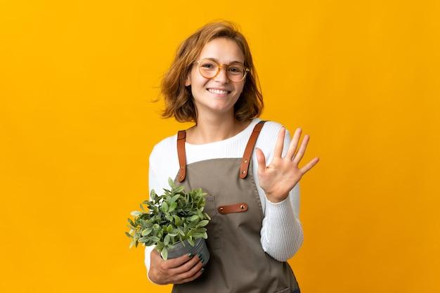 손가락으로 5 세 노란색 벽에 고립 된 식물을 들고 젊은 그루지야 여자