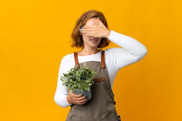 손으로 눈을 덮고 노란색 벽에 고립 된 식물을 들고 젊은 그루지야 어 여자. 뭔가보고 싶지 않아