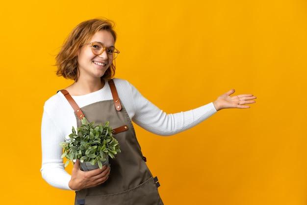 노란색 벽에 고립 된 식물을 들고 젊은 그루지야 여자가 와서 초대하기 위해 손을 옆으로 확장