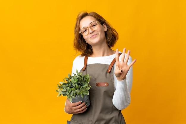 노란색 벽 행복에 고립 된 식물을 들고 손가락으로 4 세 젊은 그루지야 여자