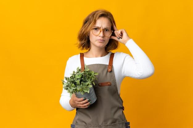 疑いと思考を持って黄色の壁に隔離された植物を保持している若いジョージ王朝様式の女性