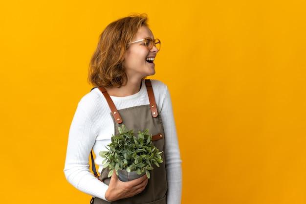 측면 위치에서 웃고 노란색 벽에 고립 된 식물을 들고 젊은 그루지야 여자