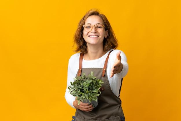 좋은 거래를 닫기 위해 악수하는 노란색 벽에 고립 된 식물을 들고 젊은 그루지야 여자