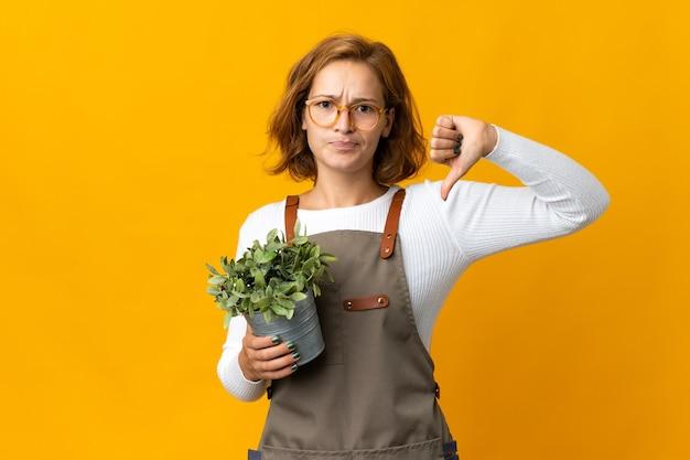 부정적인 표현으로 아래로 엄지 손가락을 보여주는 노란색 벽에 고립 된 식물을 들고 젊은 그루지야 여자