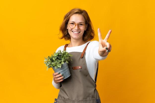 웃 고 승리 기호를 보여주는 노란색 벽에 고립 된 식물을 들고 젊은 그루지야 여자