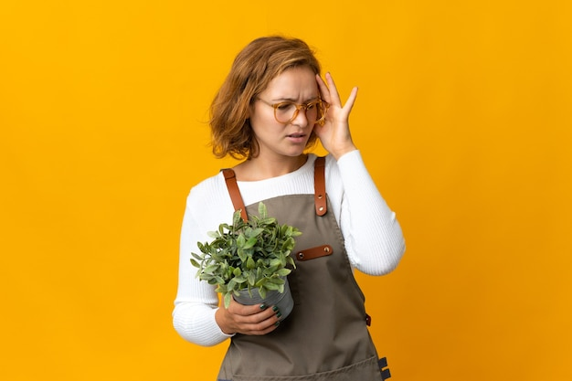 두통과 노란색 벽에 고립 된 식물을 들고 젊은 그루지야 여자