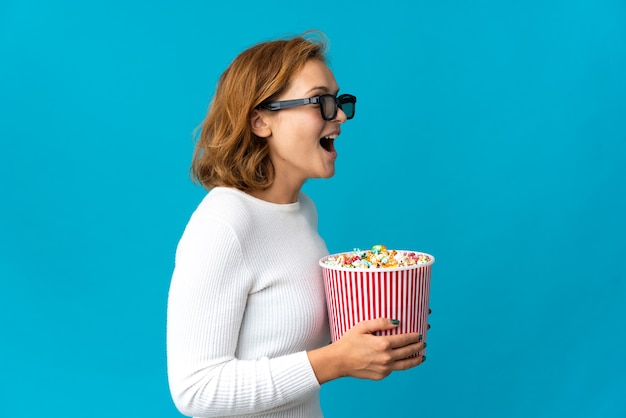 Young georgian woman isolated on blue background with 3d glasses and holding a big bucket of popcorns