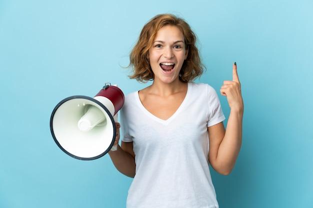 Молодая грузинская женщина изолирована на синем фоне с мегафоном и показывает прекрасную идею