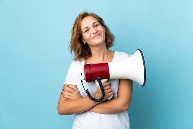 Молодая грузинская женщина изолирована на синем фоне с мегафоном и улыбается
