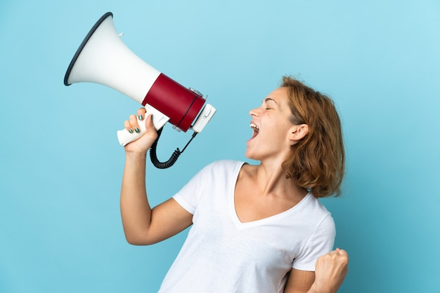 Молодая грузинка, изолированная на синем фоне, кричит в мегафон, чтобы объявить что-то в боковом положении