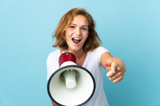 Молодая грузинка, изолированная на синем фоне, кричит в мегафон, чтобы что-то объявить, указывая на фронт
