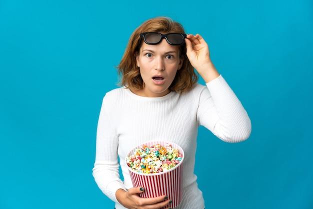 Молодая грузинская женщина, изолированная на синем фоне, удивлена 3d-очками и держит большое ведро попкорна