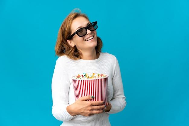 Молодая грузинская женщина изолирована на синем фоне с 3d-очками и держит большое ведро попкорна