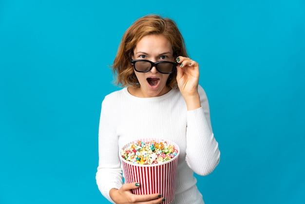 파란색 벽에 고립 된 젊은 그루지야 여자 3d 안경에 놀란 팝콘의 큰 양동이를 들고