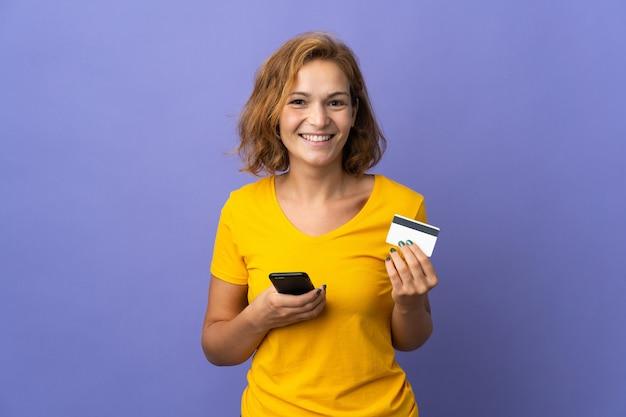 Молодая грузинская женщина изолирована на фиолетовом фоне, покупая с мобильного телефона с помощью кредитной карты