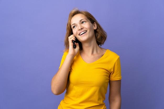 Молодая грузинская женщина изолирована на фиолетовом фоне, разговаривая с кем-то по мобильному телефону