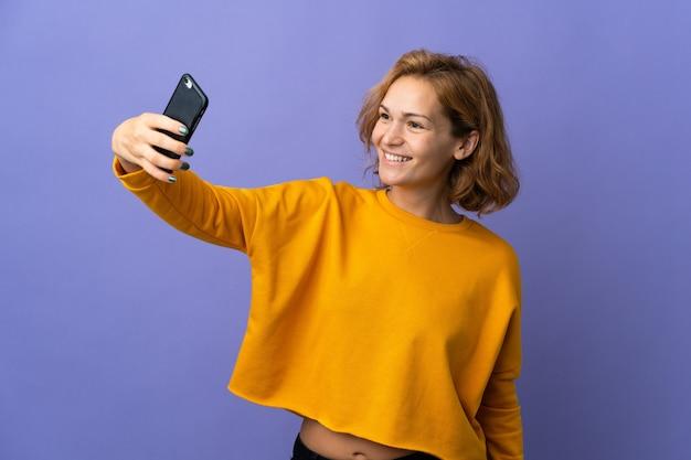 Молодая грузинская женщина изолирована на фиолетовом фоне, делая селфи