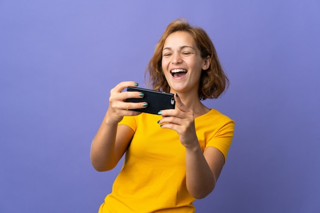Молодая грузинская женщина изолирована на фиолетовом фоне, играя с мобильным телефоном
