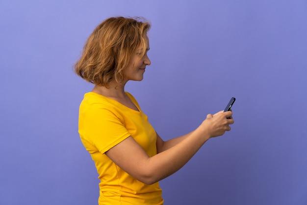 Молодая грузинская женщина изолирована на фиолетовом фоне, отправляя сообщение или электронное письмо с мобильного телефона