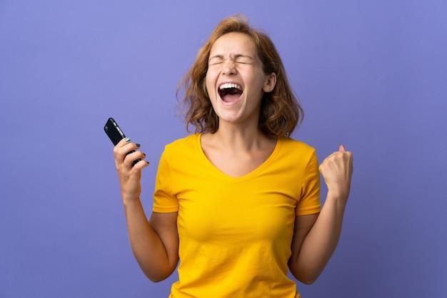 Молодая грузинская женщина изолирована на фиолетовом фоне с помощью мобильного телефона и делает жест победы