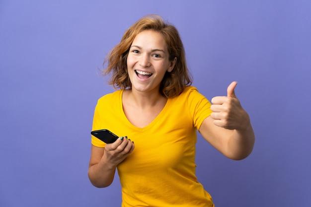 Молодая грузинская женщина изолирована на фиолетовом фоне с помощью мобильного телефона, делая большие пальцы руки вверх