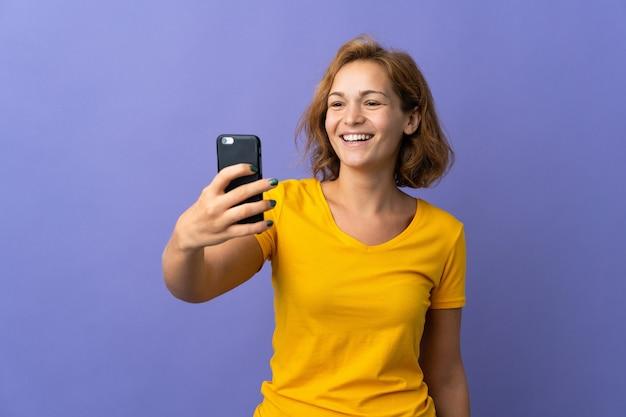 Молодая грузинская женщина изолирована на фиолетовой стене, делая селфи с мобильным телефоном