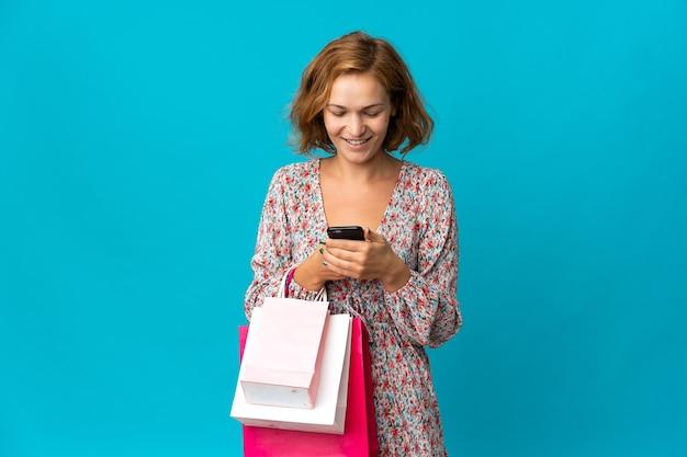 ショッピングバッグを保持し、友人に彼女の携帯電話でメッセージを書いている青い壁に分離されたショッピングバッグを持つ若いジョージ王朝時代の女性