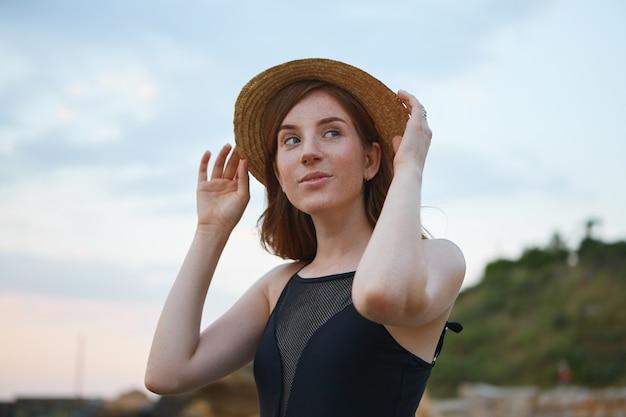 La giovane signora carina allo zenzero con le lentiggini cammina sulla spiaggia, tiene il cappello, guarda sognante la telecamera, sembra positiva e felice.