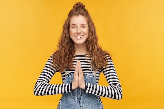 若い生姜の女性は広く微笑んで、彼女の手のひらを一緒に祈る位置に保ちます。すべてがうまくいくことを願っています。デニムのオーバーオールと剥き出しのシャツを着ています