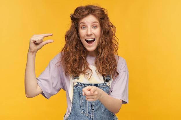 長いウェーブのかかった髪の若い生姜の女性は、片方の手で小さな何かを示し、黄色の壁の上に孤立した、笑いながらあなたを指しています。