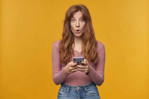 Молодая рыжая самка с веснушками изумила выражение лица, держа телефон