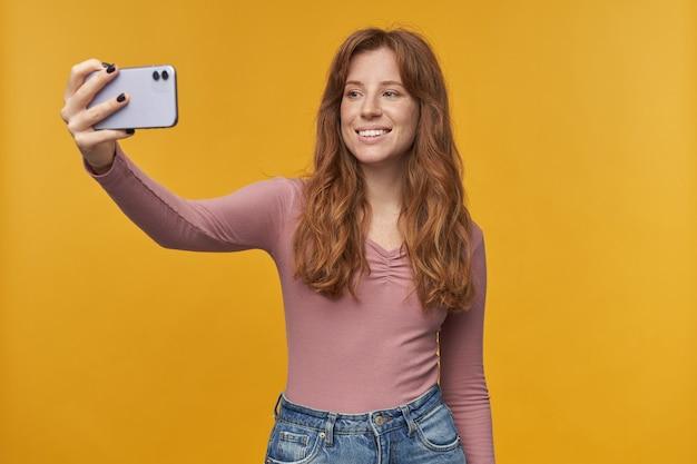 Молодая рыжая женщина с веснушками и волнистыми волосами улыбается, делая селфи