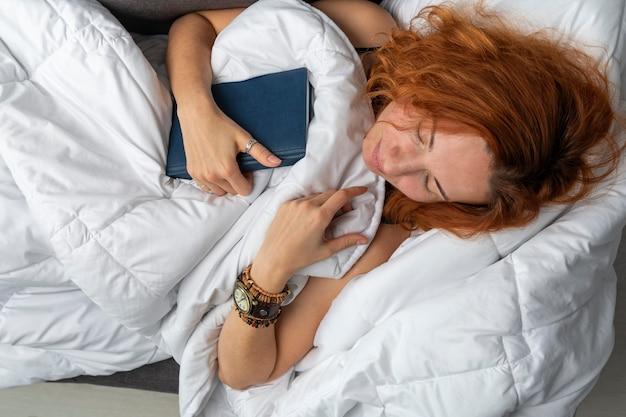 若い生姜の女の子は彼女の手で本を持って眠りに落ちました。白い毛布の下でベッドで昼寝している若い女性。