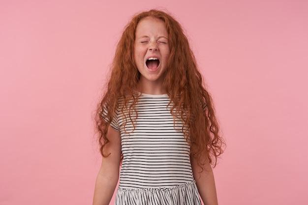 Молодая рыжая девушка кричит в камеру, закрывает глаза с отрицательным выражением лица.